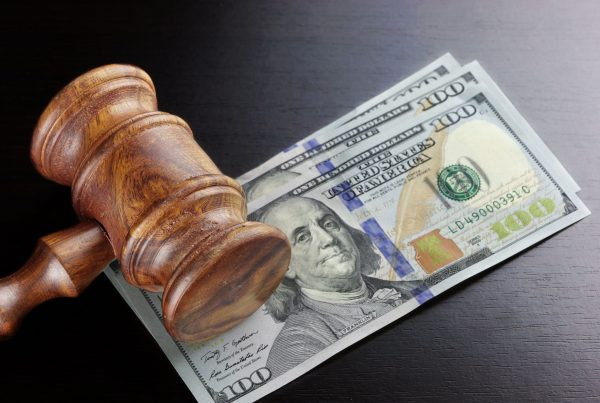Concept For Corruption, Bankruptcy, Bail, Crime, Bribing, Fraud, Auction Bidding. Judges or Auctioneer Gavel, Soundboard And Bundle Of Dollar Cash On The Rough Black Wooden Textured Table Background.