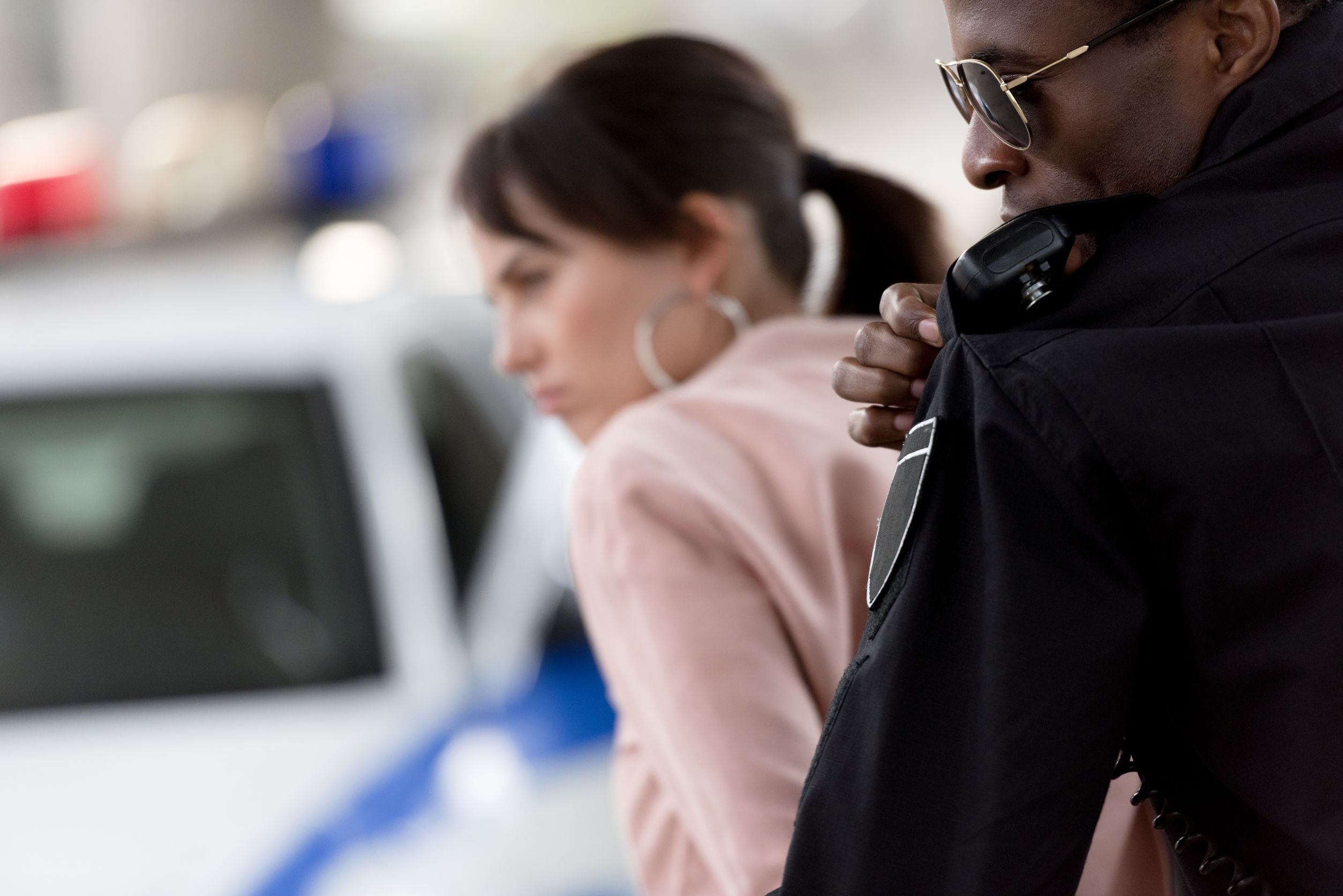 african american policeman arresting woman and talking on portable radio